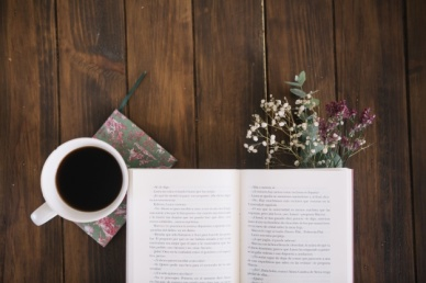 opened-book-near-coffee-and-bouquet_23-2147711390